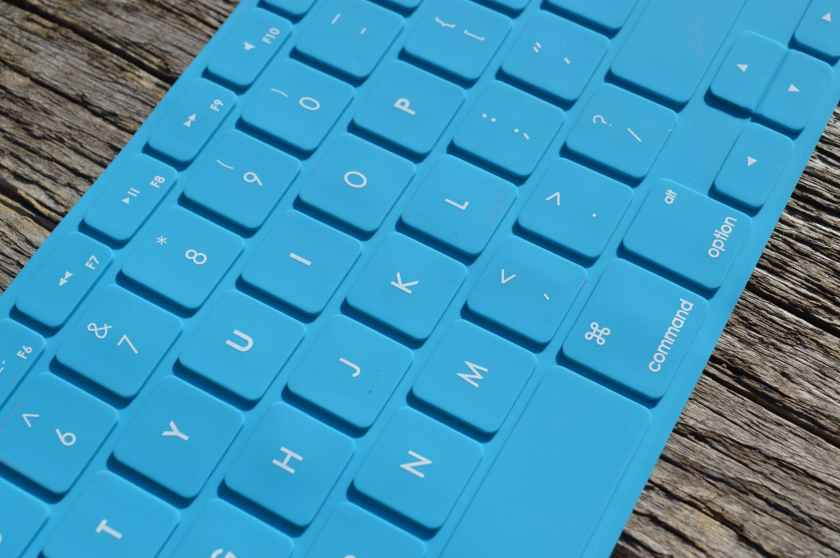 blue computer keyboard on gray wooden surface